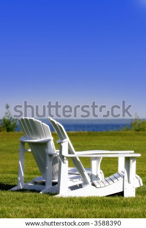 Adirondack chairs & tranquil coast – represents travel, holidays, escape, etc.  (shallow focus). - stock photo