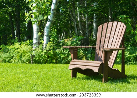Adirondack summer lawn chair outside on the green grass - stock photo