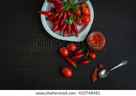 Adjika fresh grated red pepper and chili. Glass jar of homemade tomato sauce with fresh ingredients on dark wooden background. Red hot chilli pepper and ingredients for sause. Top view. Copy space. - stock photo