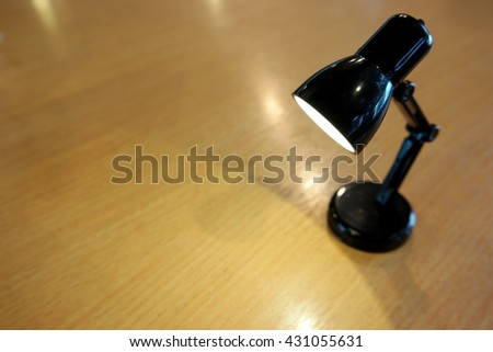 adjustable black mini small LED desk table lamp shining light to wooden table and beling lonely