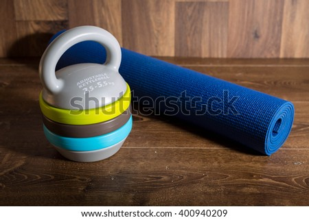 Adjustable kettlebell and mat for fitnes on wooden background. Weights for a fitness training. - stock photo