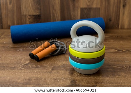 Adjustable kettlebell, jumping rope and mat for fitnes on wooden background. Weights for a fitness training. - stock photo