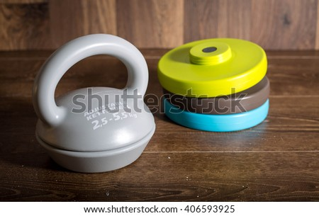 Adjustable kettlebell on wooden background. Weights for a fitness training. - stock photo
