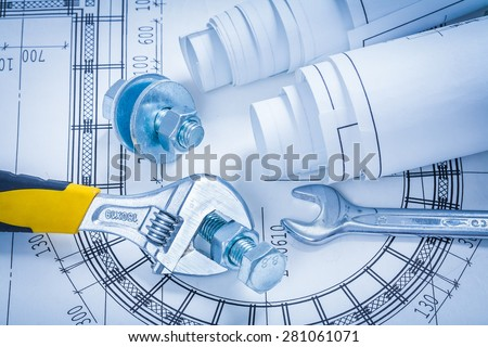 Adjustable key spanner bolts nuts and blueprints construction concept  - stock photo