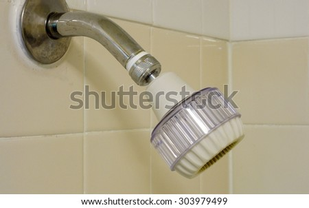 Adjustable water saving low flow shower head mounted on the wall - stock photo