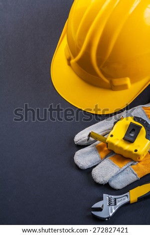 adjustable wrench protective glove tapeline helmet on black background  - stock photo
