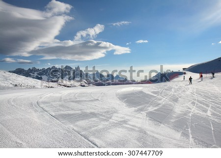 Adjusted slope on the mountain top. Skiing on the dolomites, Val di Fiemme, Italy. - stock photo