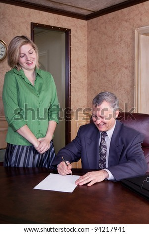 Admin getting signature from her boss - stock photo