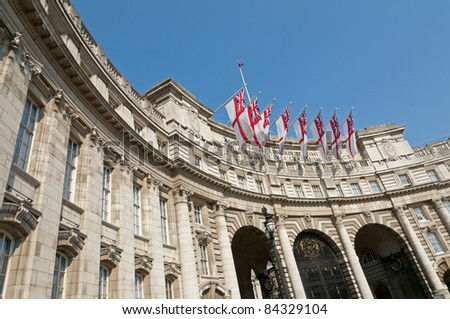 Admiralty Arch in London with eight white ensigns, the flag of the British Royal Navy, flying. - stock photo