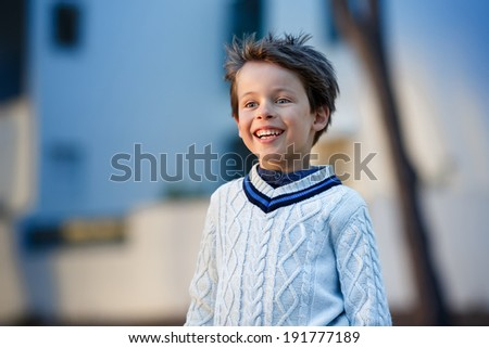 Admiring little boy laughing outdoors on summer day - stock photo