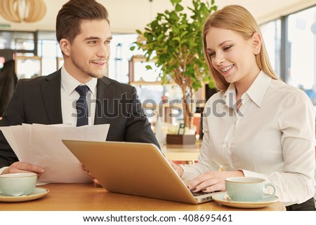 Admiring partnership. Handsome businessman smiling to his female colleague as she is typing on her laptop at the lunch in the local cafe - stock photo