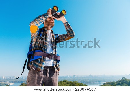 Admiring the majestic view. Handsome young bearded man carrying backpack and looking through binoculars away  - stock photo