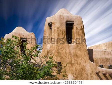 Adobe building in Santa Fe, New Mexico with cloud streaks in the sky - stock photo