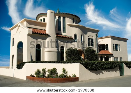 adobe style executive luxury home with blue sky and wall - stock photo