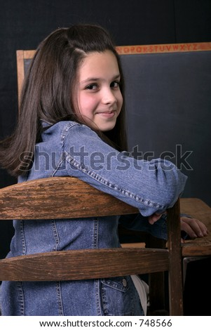 Adolescent girl sitting at desk in classroom setting - stock photo