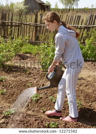 adolescent girl watering at the vegetable garden