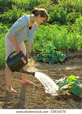adolescent girl watering vegetable bed with marrows sprouts
