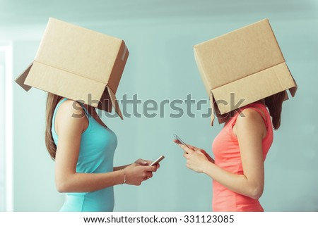 Adolescent girls with boxes on their heads texting with their smart phones, social networks and isolation concept - stock photo
