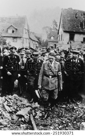 Adolf Hitler, with German military and officials, inspects bomb damage in a German city in 1944. World War 2. - stock photo