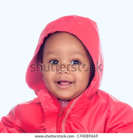 Adorable african baby with a beautiful smile and a red raincoat on a blue background - stock photo