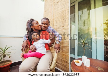 adorable african family at balcony having tea - stock photo