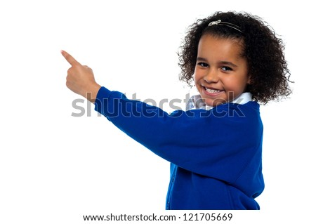 Adorable African kid pointing at copy space area while facing the camera. - stock photo