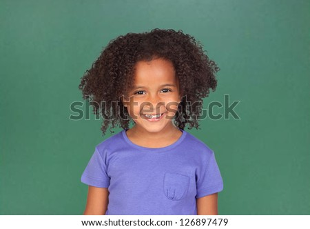 Adorable african little girl with beautiful hairstyle and a blackboard of background - stock photo
