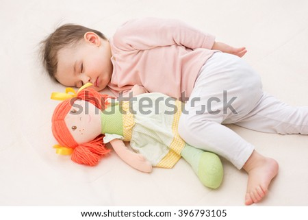 Adorable and beautiful baby toddler sleeping with a doll with orange hair.