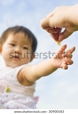 adorable and cute baby reaching out to adult's hand