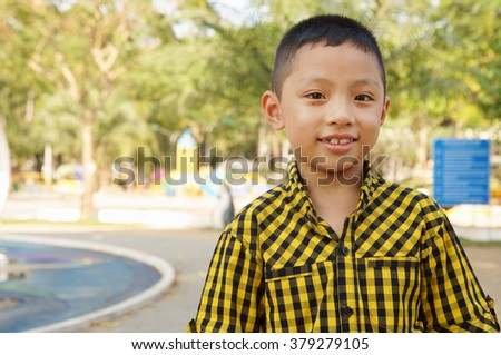 Adorable and cute boy smiling on city park background with room for text