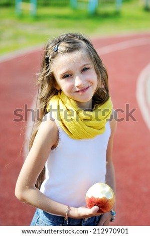 Adorable and fashion preteen girl eating apple on the school athletic field - stock photo