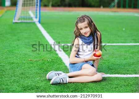 Adorable and fashion preteen girl eating apple on the school athletic field