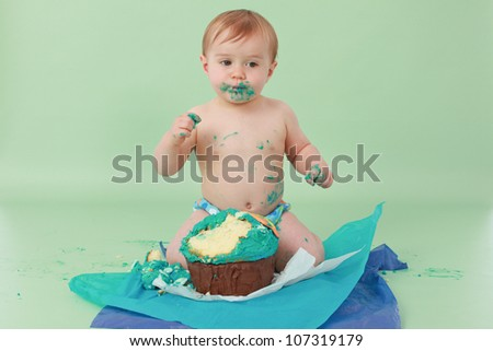 Adorable and surprised smiling brunette haired baby boy with blue butter icing on face holding cake with his sticky fingers and his ocean themed giant cupcake broken up on seamless green background - stock photo