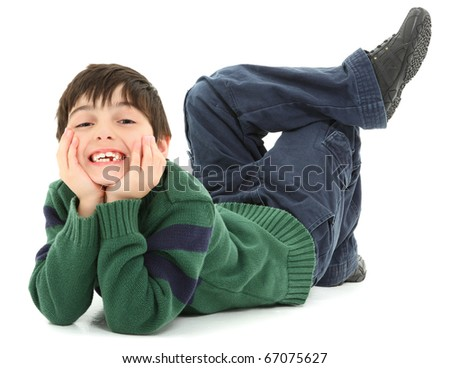 Adorable and very flexible 7 year old french american boy laying on belly with legs twisted behind him.  Smiling.