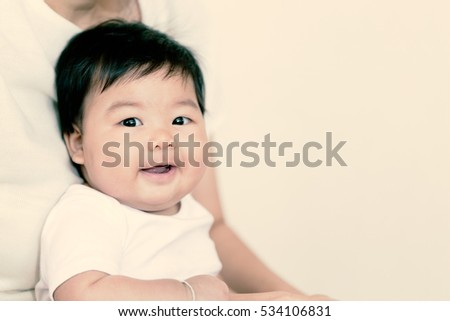 Adorable asian baby girl smiling with copy space. (Warm tone)