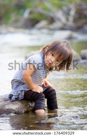 Adorable Asian baby play in the pond