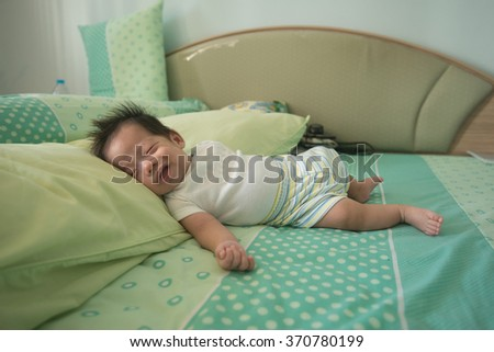 Adorable asian baby smile as he feel safe while he sleep - stock photo