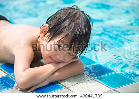 Adorable Asian child in the pool looks in a camera