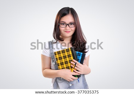 Adorable Asian nerd teenage girl holding some books and pen, on white background - stock photo