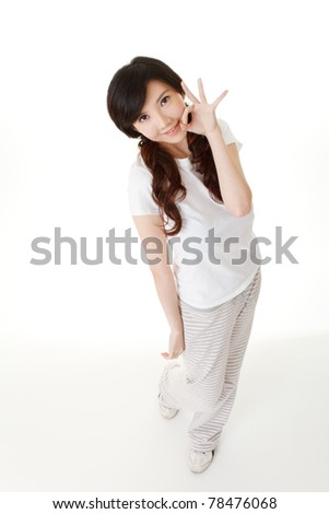 Adorable Asian woman give you ok gesture and looking at you, full length portrait in studio white background.