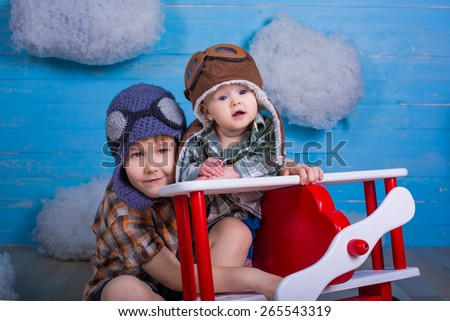 adorable babies brother and sister hugging each other in toy airplane on wooden background true emotions and feelings