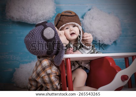 adorable babies brother and sister kissing sitting in toy airplane on wooden background true emotions and feelings - stock photo