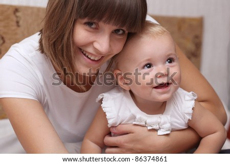 Adorable baby and mother in home