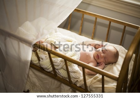 Adorable baby asleep in his cradle by a window. - stock photo