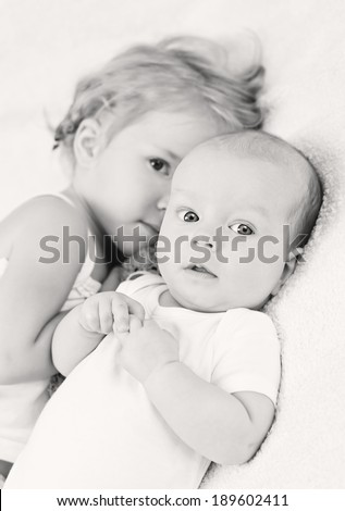Adorable baby boy and her older sister on a white background ( black and white ) - stock photo