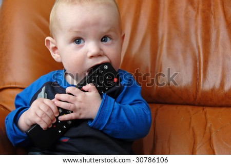 Adorable baby boy chewing a tv remote - stock photo