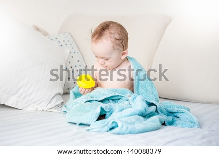 Adorable baby boy covered in blue towel playing with yellow rubber duck on sofa after bathing - stock photo