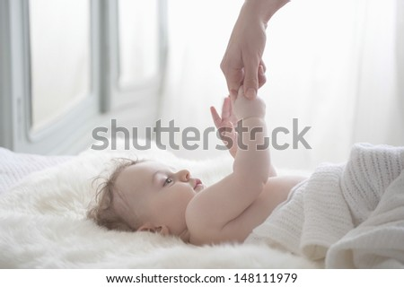 Adorable baby boy holding mother's hand in bedroom - stock photo