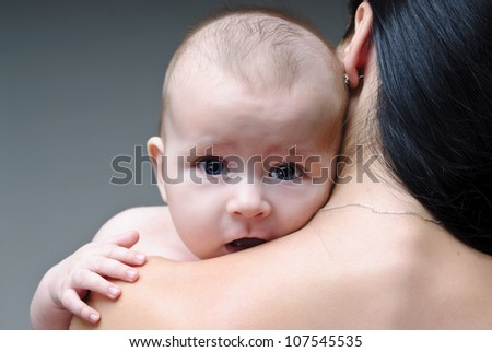 Adorable baby boy holding tight mother's neck and shoulder.