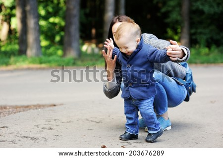 Adorable baby boy in blue coat makes his first steps with help of his beauty young mother - stock photo